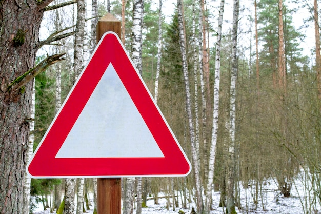 Verkeersbord in driehoekige vorm met uitroepteken in bosweg