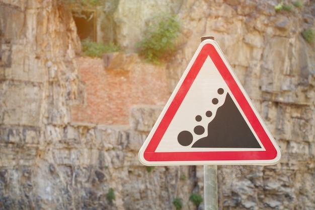 Verkeersbord let op rockfall, tegen de ruimte van een rots