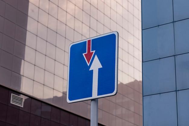 Verkeersbord op een straat in de stad tegen de achtergrond van muren van gebouwen.