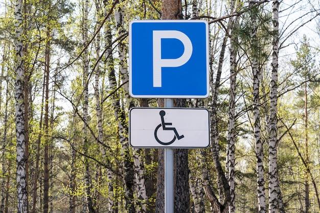 Verkeersbord parkeren voor gehandicapten in de buurt van een bos of openbaar park, tegen een tafel met bomen