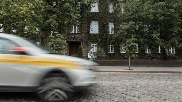 Verkeersconcept. cool jongeman toerist in trendy jeugdjeans kleding met mode stoffen tas reist op vintage stadsstraat in de buurt van oud gebouw begroeid met groene bladeren. stedelijke man loopt in de buurt van de weg.