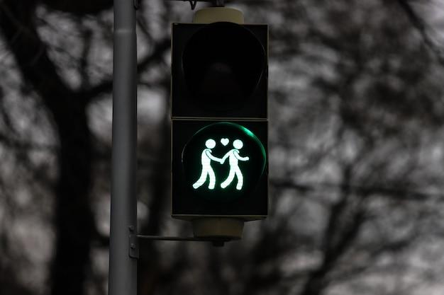 Verkeerslicht in het groen met twee verliefde mensen hand in hand in wenen.