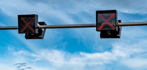 Verkeerslichtlicht met rode kleur van dwarsteken op blauwe hemel en witte wolkenachtergrond. verkeerd teken. geen ingang verkeersbord. rode kruis begeleiding stop ga verkeerslichtlicht. waarschuwing verkeerslicht.