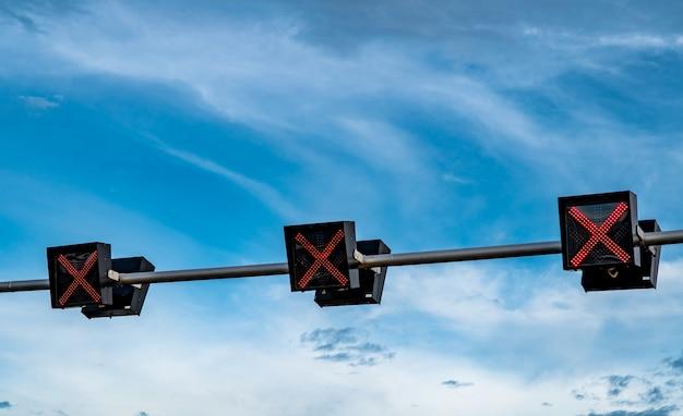 Verkeerslichtlicht met rode kleur van dwarsteken op blauwe hemel en witte wolkenachtergrond.