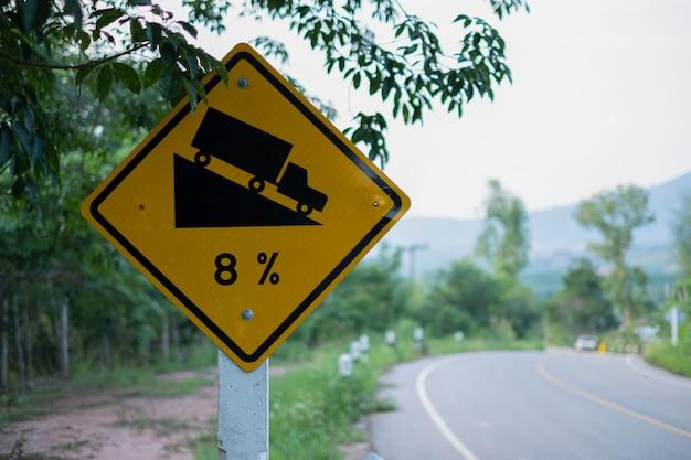 Verkeerstekens die steile verkeersteken waarschuwen om een steile helling van 8 percenten bergaf in de weg vooruit bij groen gras in de muur te hellen