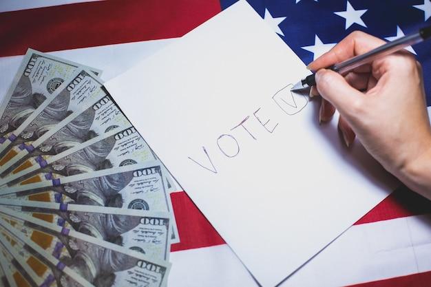 Verkiezingen in de vs. vrouw zet een vinkje op het papier om te stemmen. politieke veranderingen in het land. corruptie systeem. amerikaanse vlag en dollarsgeld. mensen stemmen op de stemming.