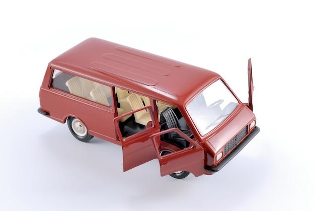 Verkleinde kopie van een rode retro-passagiersminibusauto op een witte achtergrond van metaal
