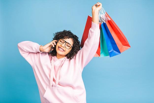 Verkoop concept! mooie zwarte afro-amerikaanse vrouw glimlachend en met boodschappentassen geïsoleerd op blauwe achtergrond. met behulp van mobiele telefoon.