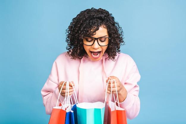 Verkoop concept! mooie zwarte afro-amerikaanse vrouw glimlachend en met boodschappentassen geïsoleerd op blauwe achtergrond.
