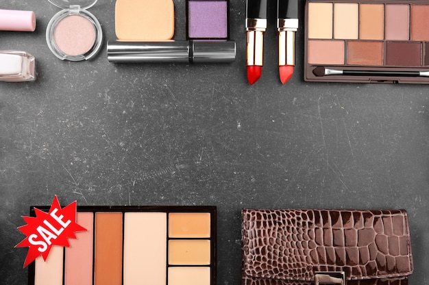 Verkoop concept. roze label met vrouwelijke spullen en cosmetica op grijze achtergrond