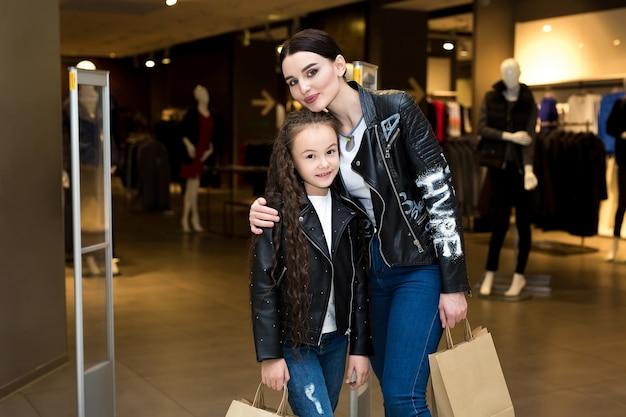 Verkoop consumentisme en mensen concept - gelukkige moeder en kind met boodschappentassen