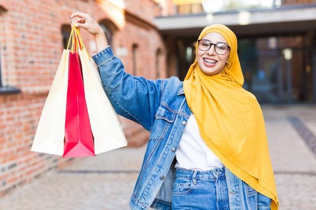 Verkoop en kopen concept - gelukkig arabisch moslimmeisje met boodschappentassen na winkelcentrum