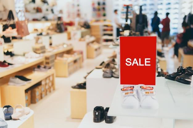Verkoop etiketstandaardsjabloon op planken in kledingwinkel of winkelfront voor verkooppromotie en kortingsinformatie.