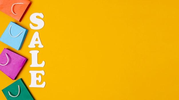 Verkoop met papieren zakken concept op oranje achtergrond en kopie ruimte