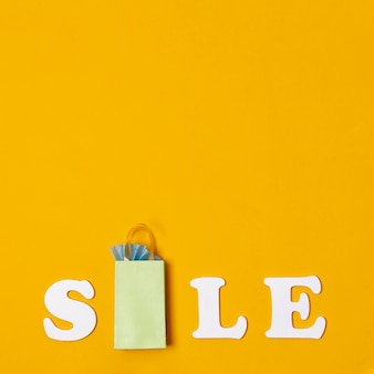 Verkoop met papieren zakken concept op oranje achtergrond