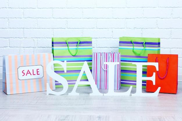 Verkoop met tassen op de vloer op een lichte achtergrond