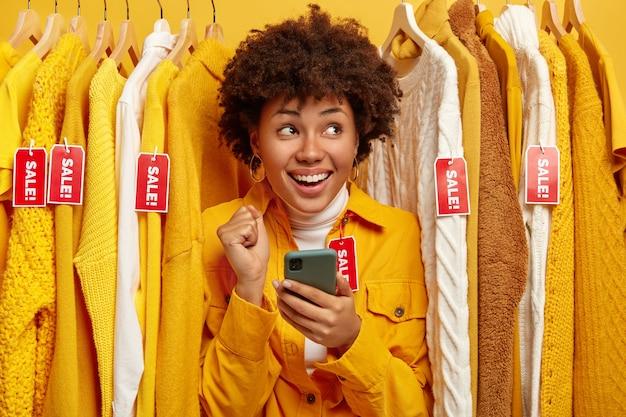 Verkoop, mode, kortingen en online winkelconcept. dolblij vrouw met donkere huid kiest kleding in kledingwinkel, verheugt zich over grote verkopen, houdt mobiel vast