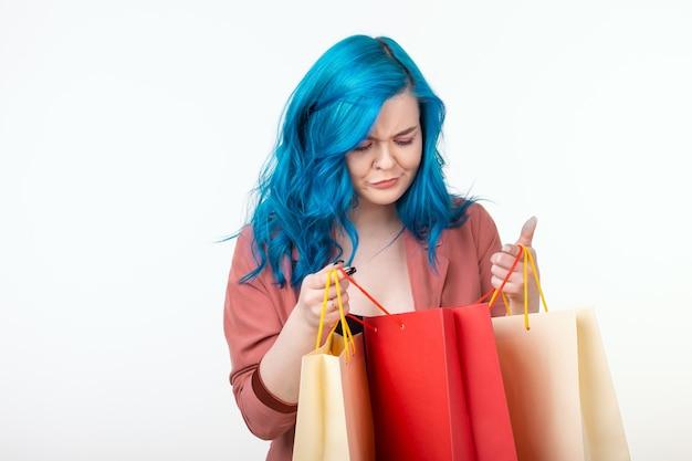 Verkoop, shopaholic en consumentenconcept - mooi meisje met blauw haar dat zich met boodschappentassen op witte achtergrond bevindt.