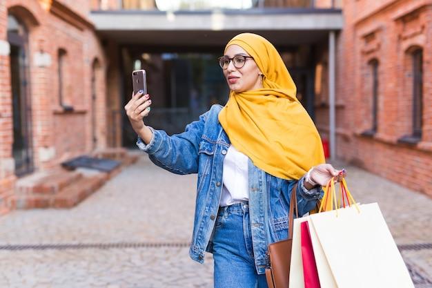 Verkoop, technologieën en koopconcept - gelukkige arabische moslimvrouw die daarna selfie buiten neemt