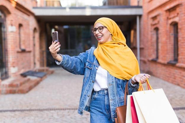 Verkoop, technologieën en koopconcept - gelukkige arabische moslimvrouw die na het winkelen selfie buiten neemt