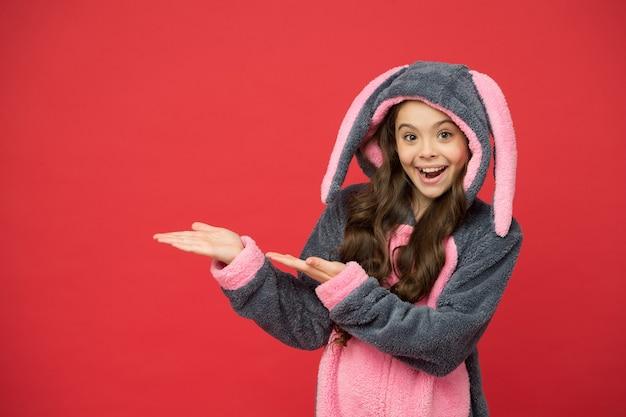 Verkoop van producten. gelukkig meisje in konijnenpyjama toont lege handen voor product. product presenteren. product promotie. verkoop en korting. promotie en marketing. uw reclame, kopieer ruimte.