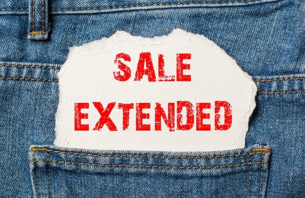 Verkoop verlengd op wit papier in de zak van blauwe spijkerbroek