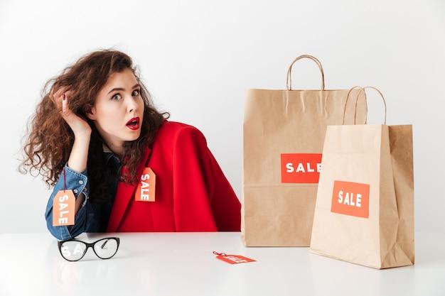 Verkoop vrouw zitten aan de tafel met papieren boodschappentassen