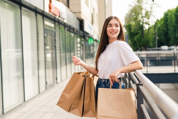 Verkoop, winkelen, toerisme en gelukkige mensen concept - mooie vrouw met boodschappentassen in de stad