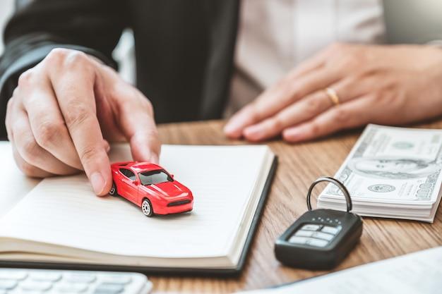 Verkoopagent die auto aan klant geeft en overeenkomstovereenkomst, verzekeringsauto ondertekent.