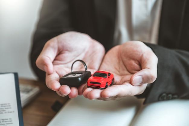 Verkoopagent die autosleutel geeft aan klant en overeenkomstcontract, verzekeringsauto ondertekent.