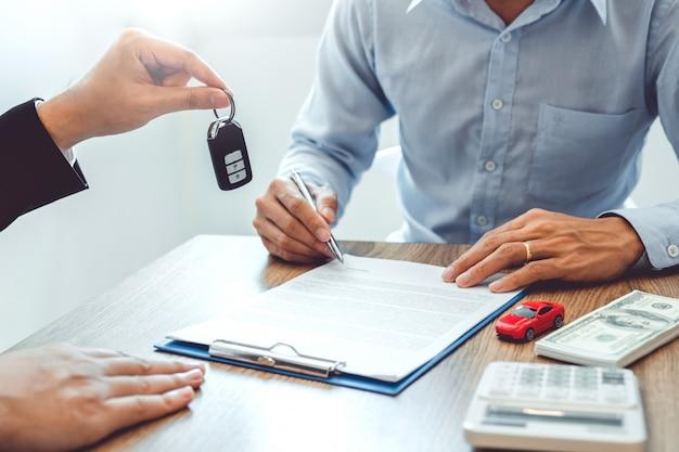 Verkoopagent die autosleutel geeft aan klant en overeenkomstovereenkomst ondertekent