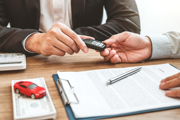 Verkoopagent die autosleutel geven aan klant en overeenkomstcontract, het concept van de verzekeringsauto ondertekenen.