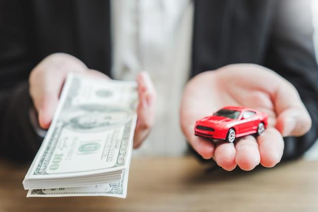Verkoopagent met rekeningen en speelgoedauto op zijn handen