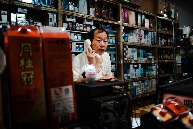 Verkoopbediende in kleine taiwanese winkel die aan de telefoon praat