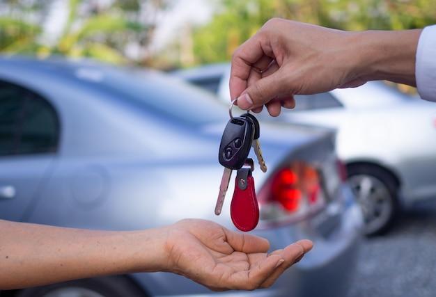 Verkoopbureaus verkopen auto's en geven sleutels aan nieuwe eigenaren. auto of huurauto verkopen