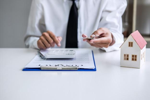 Verkoopmanager die sleutels bewaart bij de klant na ondertekening van het huurcontract van de koopovereenkomst