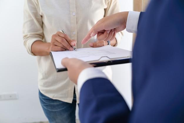 Verkoopmanager geeft advies aanvraagformulier document, rekening houdend met hypotheekaanbod voor auto- en woningverzekering.