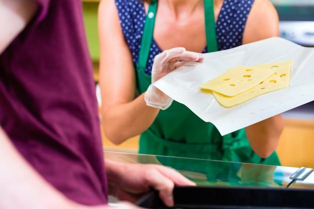 Verkoopster bij teller die kaas aanbiedt