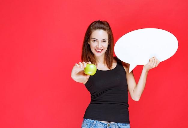 Verkoopster die een groene appel en een ovaal infobord vasthoudt en de appel aan de klant geeft