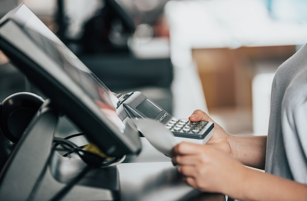 Verkoopster die procesbetaling op kaartterminal doet aan een klant in het winkelcentrum, pos