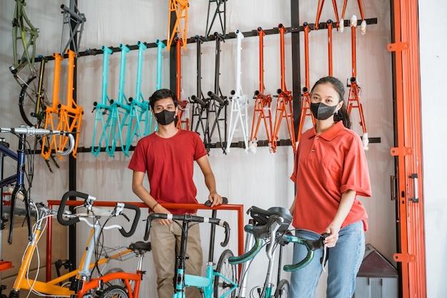Verkoopster en verkoper met zwart masker kijken naar camera in fietsenwinkel