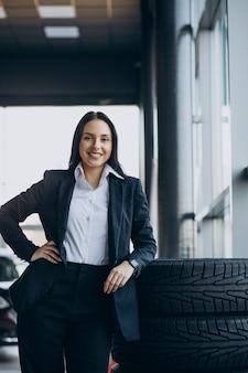 Verkoopster in autotoonzaal die auto's verkoopt