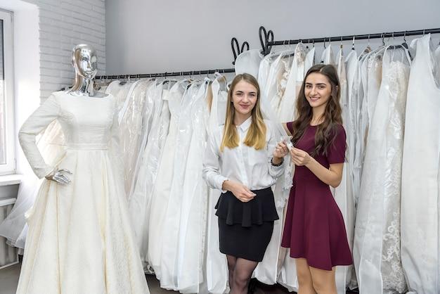 Verkoopster in huwelijkssalon die jonge bruid helpen