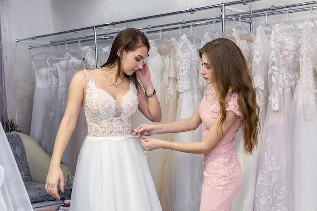 Verkoopster in trouwsalon die jonge bruid helpt