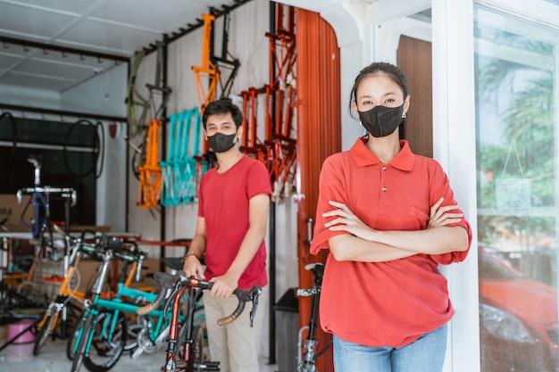 Verkoopster met masker die naar camera kijkt met gevouwen handen en een man die een fiets vasthoudt