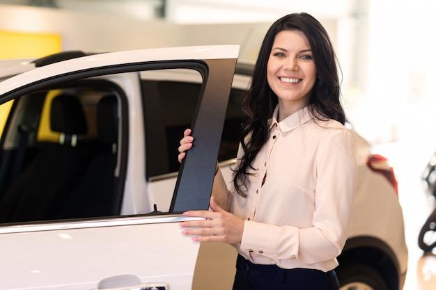 Verkoopster met sleutel presenteert een nieuwe auto in dealercentrum