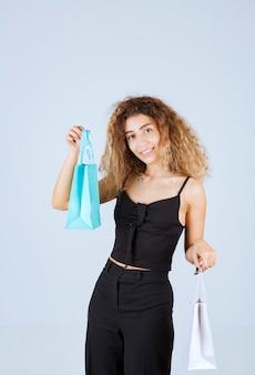 Verkoopster pakte de kleurrijke boodschappentassen in en gaf aan de klant.