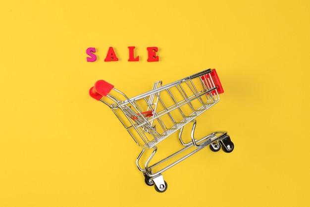 Verkooptekst en winkelwagen op een geel oppervlak