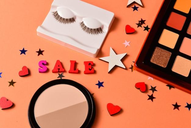 Verkooptekst op een oranje achtergrond. professionele trendy makeup producten met cosmetische schoonheidsproducten, oogschaduws, wimpers, borstels en tools.