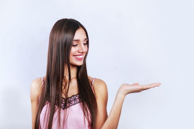 Verkooptijd, kortingen voor 14 februari, leuke, schattige brunette vrouw met kopie ruimte op haar handpalm, op zoek naar kant